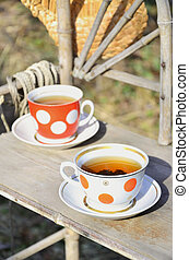 Rustic still life with a cups of tea and straw hat - A...