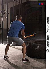man workout with hammer and tractor tire