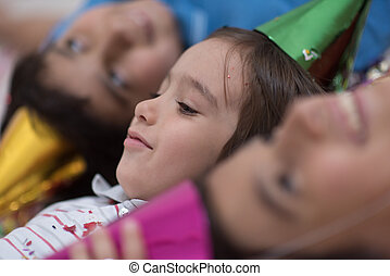 kids  blowing confetti while lying on the floor