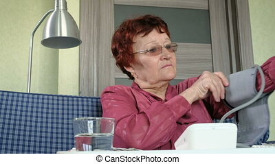 Mature lady examining her health state with manometer....