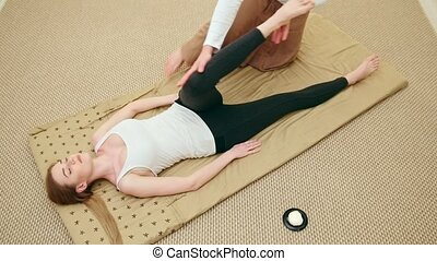 Blonde female gets massage care for muscles of legs, top...