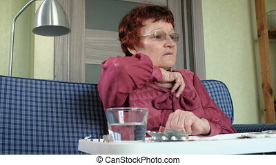 Old woman with fever checking mercury thermometer at home