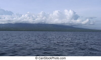 Water surface background of shore and white clouds in sky on sea in Philippines.
