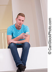 man sitting on balcony at home - portrait of a smiling young...