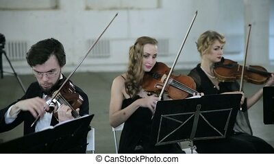 Three violinists and conductor playing music - Violinists...