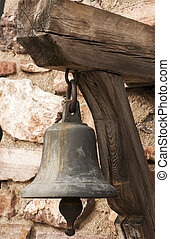Small church bell closeup on old stone wall background