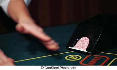 Dealer in casino deals the cards by the card feeder