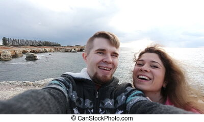 Successful traveling couple in love taking a selfie on the beach