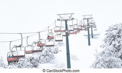 Ski lift in mountain resort - People are lifting on ski-lift...