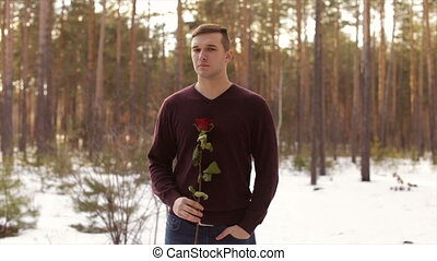 A man with a red rose in the winter forest.Slow motion