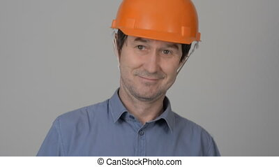 Cheerful builder in a yellow helmet invites. Portrait of a...