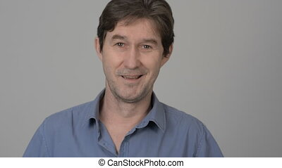 Man unshaven smiling in the studio on a light background. A...