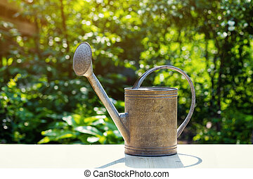 Watering can on the terrace in the garden