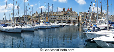 The view of yachts moored in harbor in Dockyard creek with Singlea peninsular on background. Malta