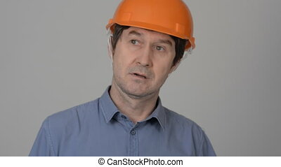 Serious construction worker with protective yellow helmet...