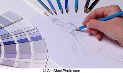 Designer dress decorates a sketch in blue, on a table cloth...