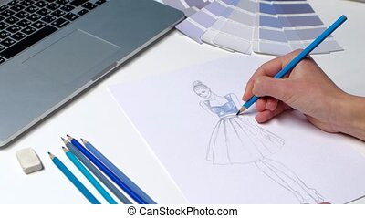 Designer with a pencil sketch decorates dresses in blue....