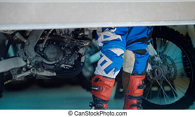 Boots of MXgirl in the garage with dirtbike, telephoto