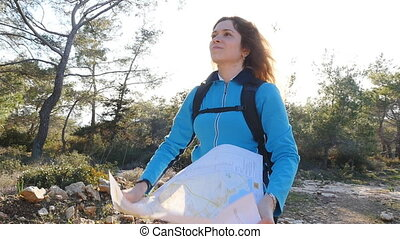 Woman hiker reading a map next to stream