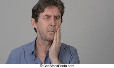 An adult man with a toothache holds a check hand on a light...