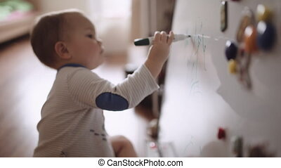 Baby draws on marker board - Baby sitting on the floor and...