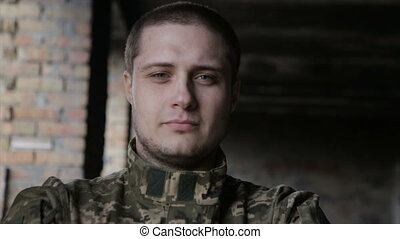 A man in military uniform on an abandoned building - A man...
