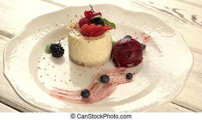 Small cake on plate. Dessert with berries. Cheesecake...