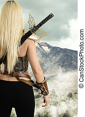 back of female warrior looking at mountain with fog