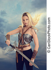 female warrior with sword and hair blowing in wind and...