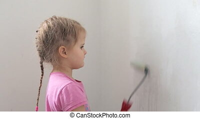 Girl with paint roller priming white wall