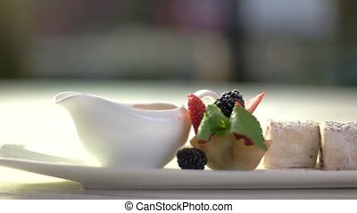 Dessert on long plate. Jug and tartlet with berries. Sweet...