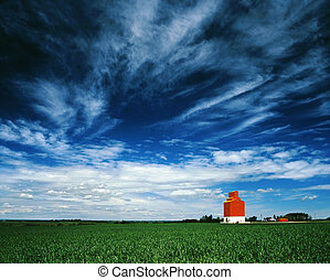 Orange grain elevator against a big blue sky. - A lone grain...