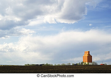 Grain elevator and cultivated dirt field - An orange grain...