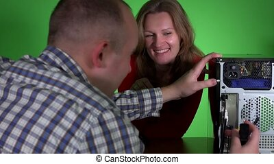 Office girl flirt with colleague guy repairing desktop pc at...