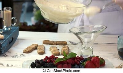 Table with tiramisu ingredients. Chef holding spoon with...