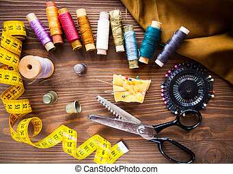 Scissor, buttons, zip, tape measure, thread and thimble on fabrics on dark wooden background, flat lay.