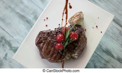 Meat on plate spinning. Grilled tenderloin steak with...