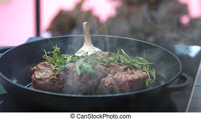 Steak and herbs on pan. Flipping the steak. Five minutes on...