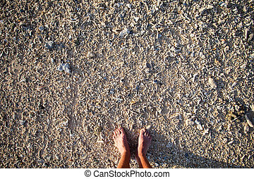 Male bare feet on the beach of the small coral