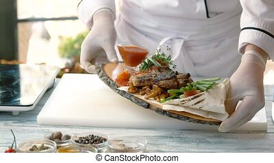 Chef holding cooked food. Grilled pork steak and vegetables....