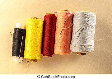 Thread bobbins and needles on paper background