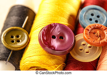 Thread bobbins, buttons and needles on paper background