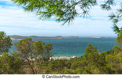 View out to sea through naturally framing trees.  San Antonio Sant Antoni de Portmany in the Balearic Islands, Ibiza.