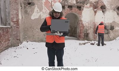 Construction engineer using laptop and walking