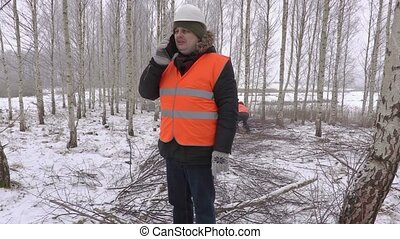 Lumberjack talking on smart phone in birch grove at branches