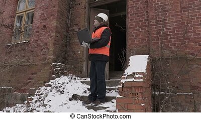 Building inspector using laptop near old building