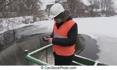Engineer using tablet near floodgate