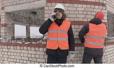 Builders talking on smart phone near unfinished building