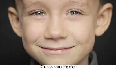 Portrait of a boy close-up on a black background. Full hd...
