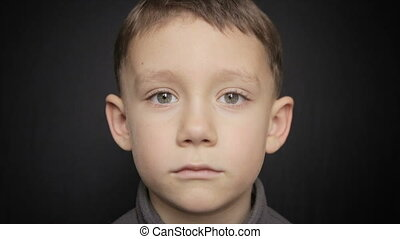 Portrait of a boy close-up on a black background. Full hd video